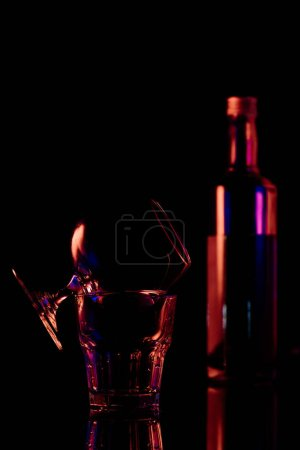 close up view of bottle and glasses with sambuca alcohol drink on black background