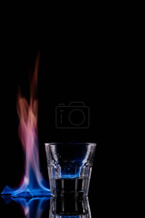 close up view of glass of burning sambuca drink on black background