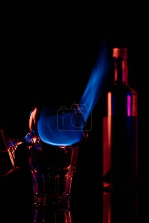 Photo for Close up view of alcohol sambuca drink burning in glass on black background - Royalty Free Image