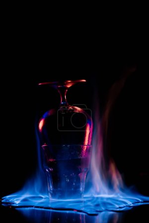 Photo for Close up view of glasses and burning sanbuca alcohol drink around on black background - Royalty Free Image