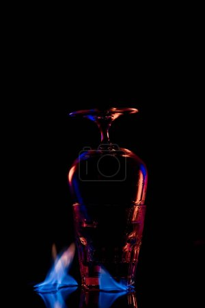 close up view of glasses and burning sanbuca alcohol drink around on black background