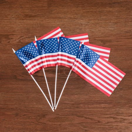 top view of row of united states flags on wooden tabletop, Independence Day concept