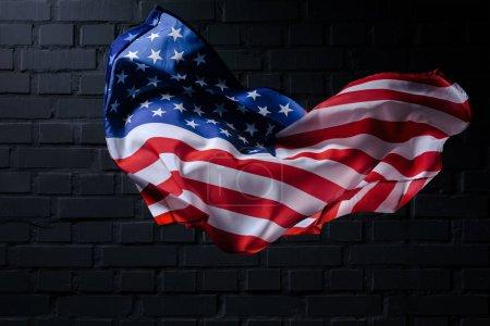 Photo pour Dynamique drapeau des États-Unis ondulant devant le mur de brique noire, concept de la fête de l'indépendance - image libre de droit