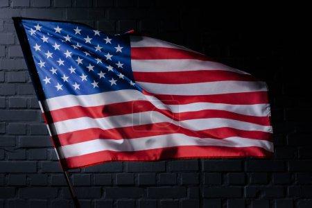 Photo pour Agitant le drapeau usa devant le mur de brique noire, concept de la fête de l'indépendance - image libre de droit