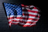 dynamic waving usa flag in front of black brick wall, Independence Day concept