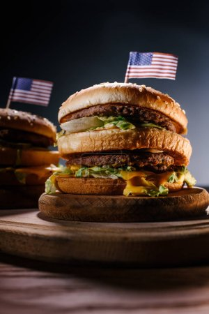 close-up shot of tasty burgers with usa flag pins on wooden cutting board on black