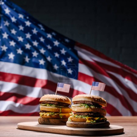 tasty burgers on wooden cutting board in front of waving united states flag