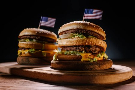 close-up shot of delicious burgers with usa flag pins on wooden cutting board on black