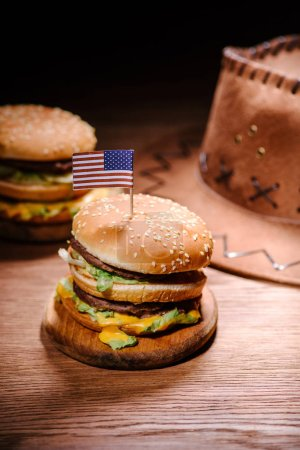 tasty burgers on wooden table with american cowboy hat