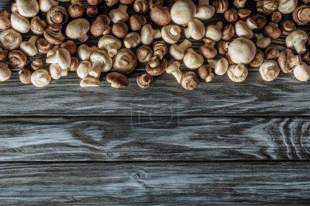 Draufsicht auf verschiedene rohe Champignon-Pilze auf Holzoberfläche