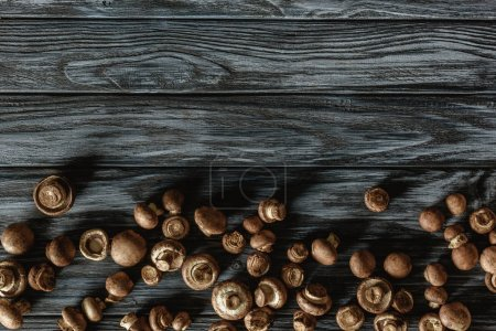 top view of row champignon mushrooms on grey wooden surface