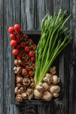 top view of champignon mushrooms with leeks and cherry tomatoes in box on wooden tabletop