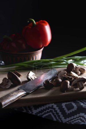 close-up shot of raw sliced champignon mushrooms with knife on wooden cutting board on black