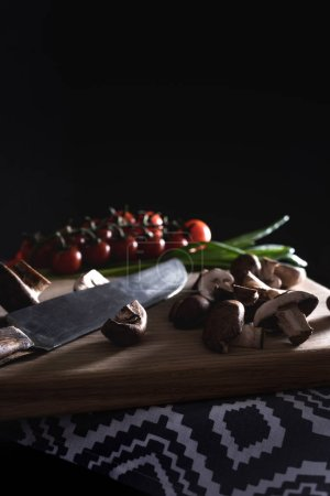 close-up shot of champignon mushrooms with knife on wooden cutting board on black