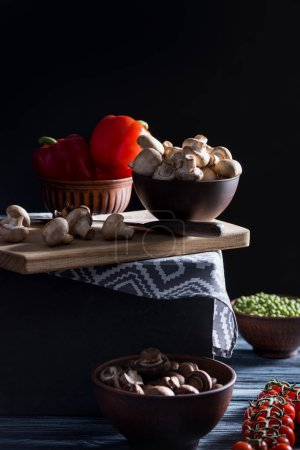 champignon mushrooms and different vegetables on table on black