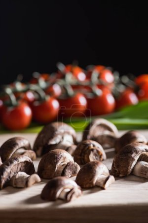 close-up shot of halved champignon mushrooms on wooden cutting board on black