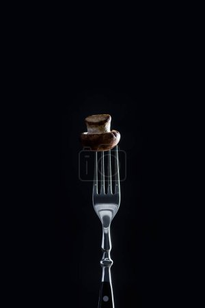 raw champignon mushroom on fork isolated on black