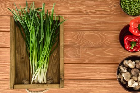 top view of leeks in box and various vegetables on wooden tabletop