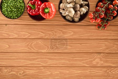 top view of champignon mushrooms and various vegetables in bowls on wooden tabletop