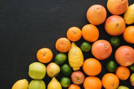 Photo pour Vue de dessus de divers fruits mûrs sur la surface noire - image libre de droit