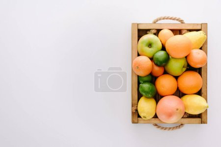 top view of various ripe fruits in wooden box on white surface