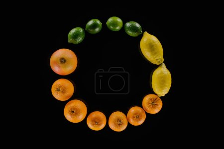 top view of various citrus fruits composition in round shape isolated on black