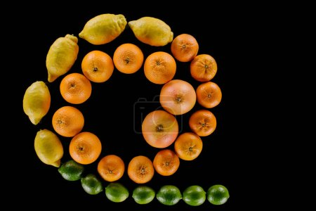 top view of various fresh citrus fruits composition in spiral shape isolated on black