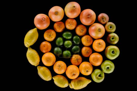 top view of various ripe citrus fruits composition in spiral shape isolated on black