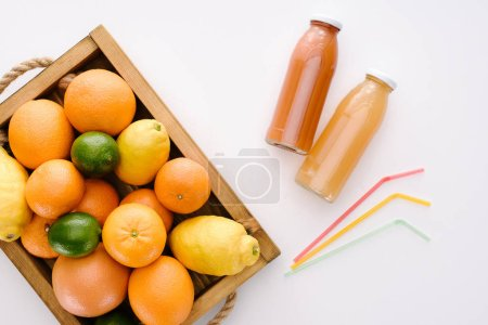 top view of various citrus fruits with bottles of juice on white tabletop