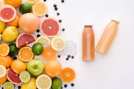 top view of various citrus fruits with bottles of juice on white surface