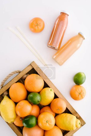 top view of various citrus fruits in wooden box with bottles of juice on white surface