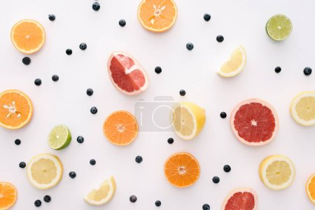 top view of citrus fruits slices and blueberries on white surface