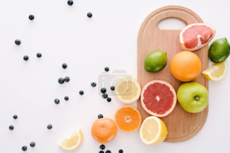 top view of citrus fruits with blueberries and wooden cutting board on white surface
