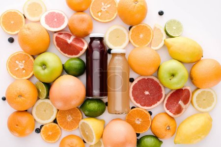 Photo pour Vue de dessus des bouteilles de jus de fruits frais avec des tranches d'agrumes mûrs sur surface blanche - image libre de droit