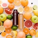 Top view of bottles of fresh juice with ripe citru...
