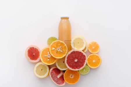 top view of bottle of juice with citrus fruits slices on white surface
