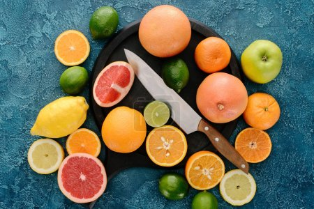top view of plate in shape of skillet and knife with citrus fruits slices on blue concrete surface