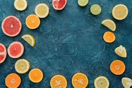 top view of citrus fruits sliced in round shape on blue concrete surface