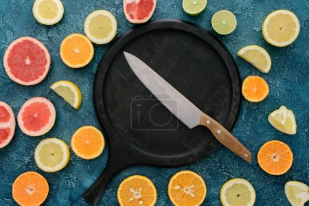 top view of plate in shape of skillet and knife surrounded with citrus fruits slices on blue concrete surface