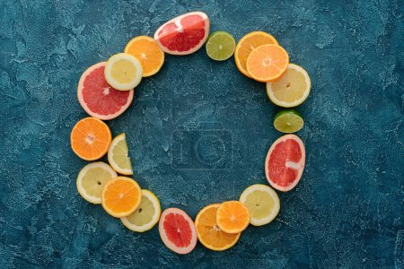 top view of round frame made of citrus fruits slices on blue concrete surface