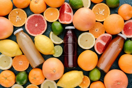 top view of glass bottle of fresh juice surrounded with citrus fruits slices on blue concrete surface