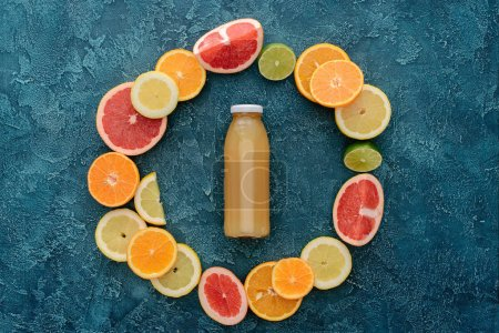top view of bottle of fresh juice surrounded with ripe citrus fruits slices in circle shape on blue concrete surface