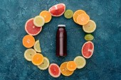 top view of bottle of fresh juice surrounded with citrus fruits slices in circle shape on blue concrete surface