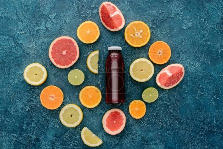 top view of bottle of red juice surrounded with citrus fruits slices on blue concrete surface
