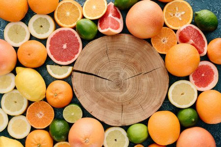 top view of wooden slice surrounded with citrus fruits slices on blue concrete surface