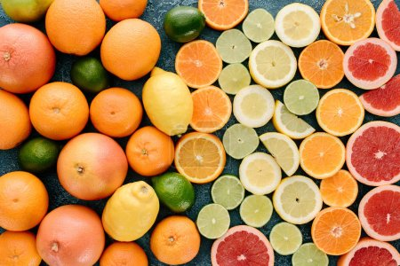 top view of various whole and sliced citrus fruits on blue concrete surface