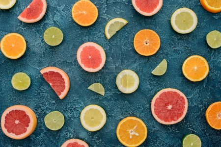 top view of ripe citrus fruits slices on blue concrete surface