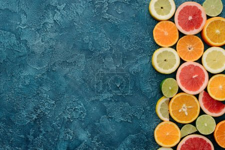 top view of fresh citrus fruits slices on blue concrete surface