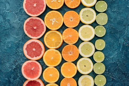 top view of various citrus fruits slices in rows on blue concrete surface