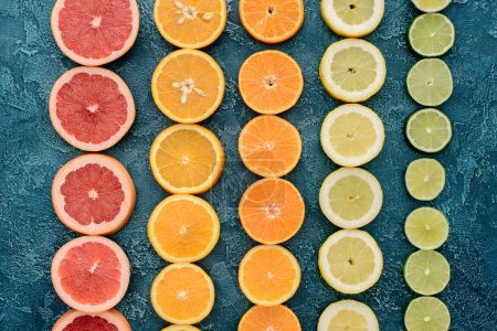 top view of citrus fruits slices in rows on blue concrete surface
